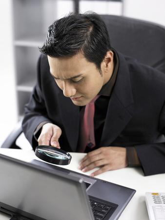 uomo con lente di ingrandimento sul laptop Archivio Fotografico