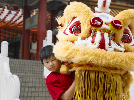 boy in red shirt lifting lion head Stock Photo