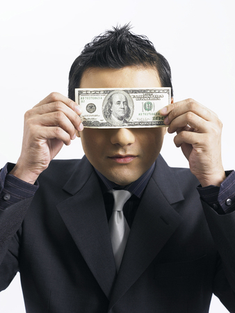 businessman holds a note bill over his eyes Imagens