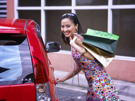 Young woman getting into car, looking at camera Stock Photo