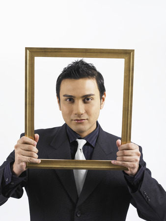 businessman holding wooden frame