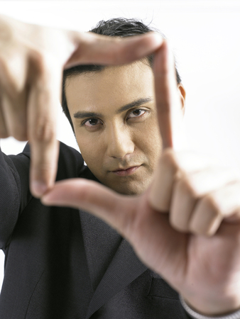 Young businessman looking through finger frame