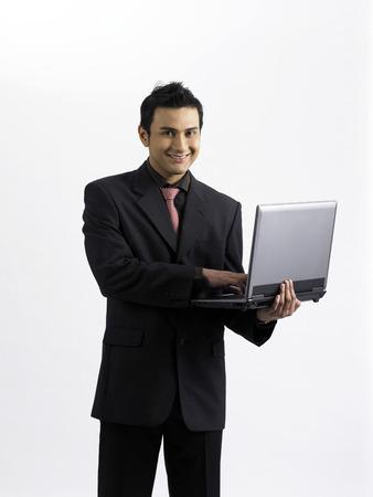 businessman holding laptop, smiling