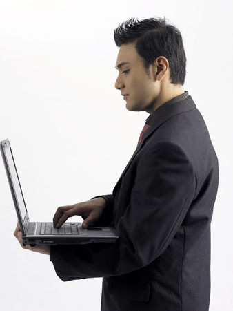 profile of businessman holding laptop