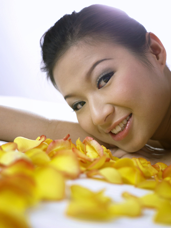 woman lying on the bed with rose petal around her Stock Photo
