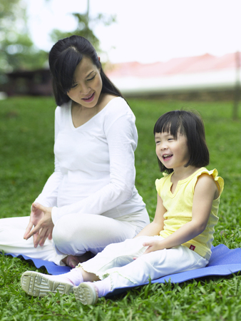 mother and daughter sitting on yoga mat