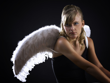Young adult seated with angel wings Stock fotó