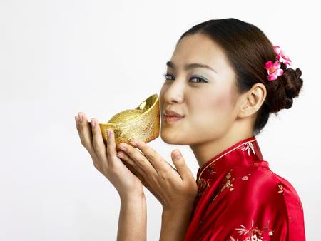 woman kissing gold ingot