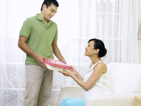 husband giving pregnant wife a present Stockfoto - 118976432