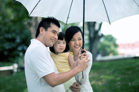 family holding umbrella in the park Imagens