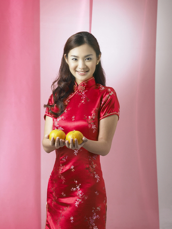 young woman offering mandarin oranges