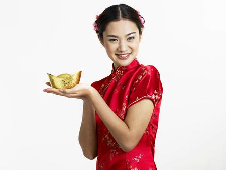 woman holding gold ingot