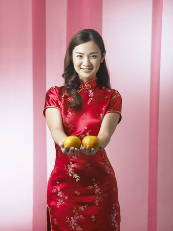 long shot of woman holding mandarin oranges Stock Photo