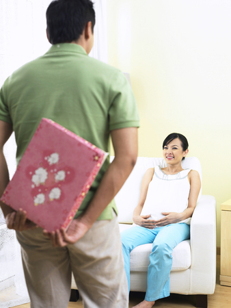 man giving his pregnant wife a surprise gift Stockfoto - 118984497