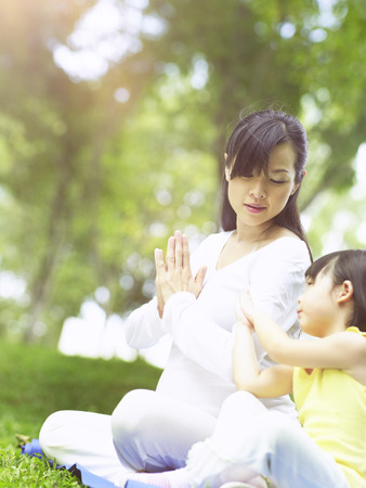pregnant woman practising yoga with little girl 免版税图像