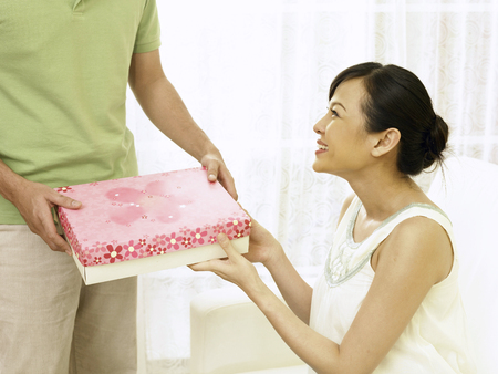 pregnant woman receiving present from husband Stockfoto