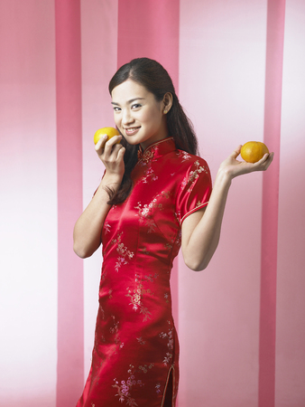young woman holding mandarin oranges Stock Photo
