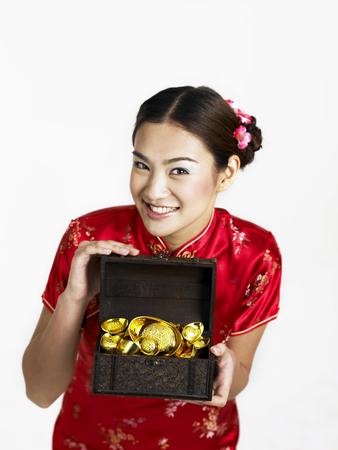 woman holding box full of gold ingots