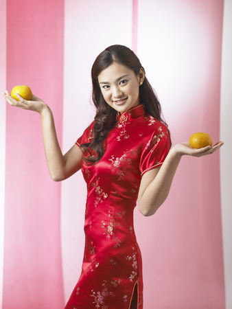 young woman with mandarin oranges in both hands