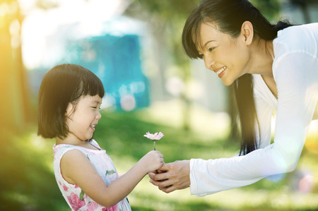girl giving flower to her mother