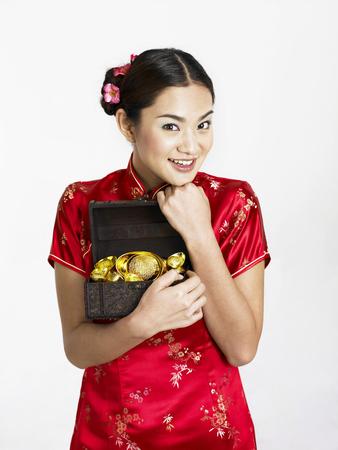 woman in cheongsam with a box of gold Archivio Fotografico