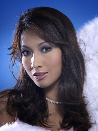 Head shot of female holding angel wings Stock Photo