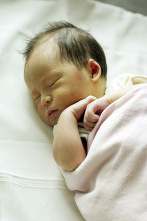 Newborn baby sleeping in its cot
