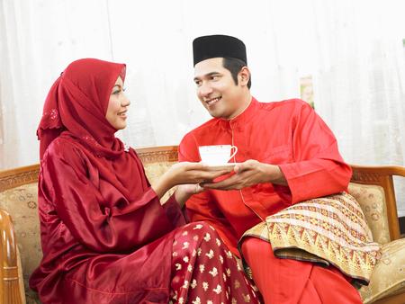Malay couple having coffee, sitting on sofa Stock Photo