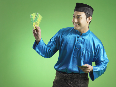 Malay man giving out duit raya Banco de Imagens - 118984572