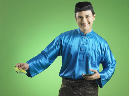 Malay man giving out duit raya