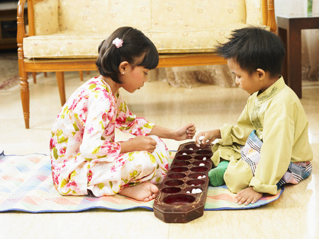a boy and girl playing traditional congkak Фото со стока