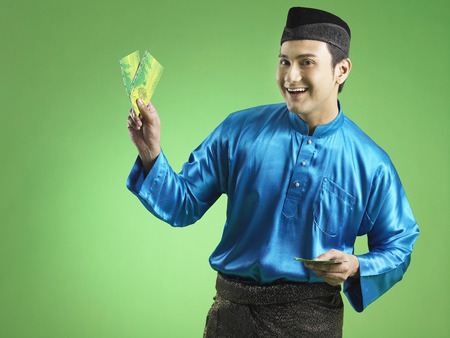 Malay man giving out duit raya Banco de Imagens - 119001291