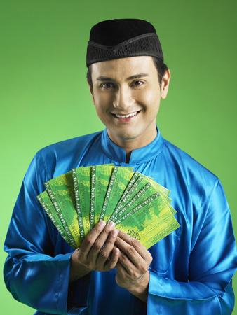 Malay man giving out duit raya Banco de Imagens - 118794454