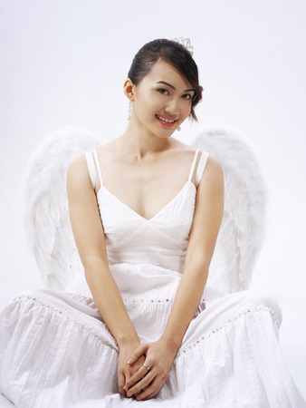 Full view of seated angel in white background