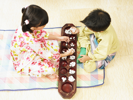 un niño y una niña jugando congkak tradicional Foto de archivo