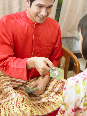 Daughter receiving green envelop from father