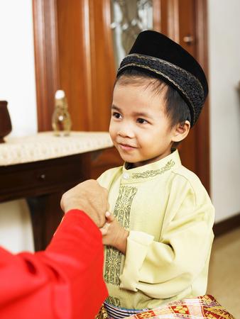 Little boy receive duit raya Banco de Imagens