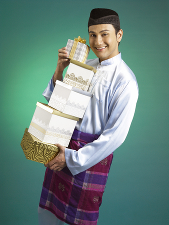 Malay man holding stack of gifts Foto de archivo