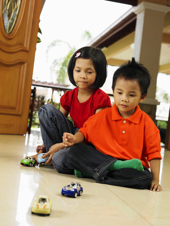 boy and girl playing toy cars together Stock fotó