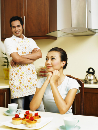 Husband looking at wife, in the kitchen