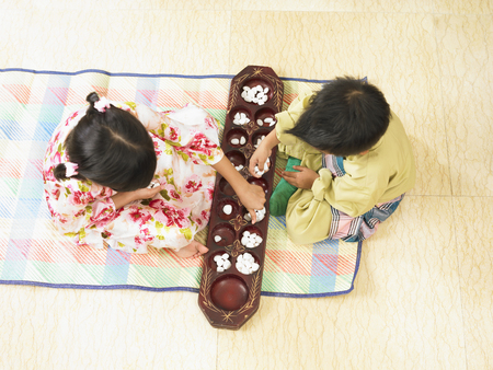 a boy and girl playing traditional congkak 스톡 콘텐츠