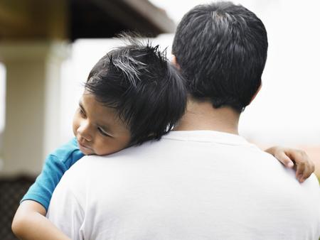 Son asleep on father shoulder Standard-Bild