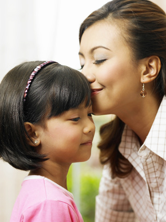 woman kissing forehead of her young daughter Stockfoto