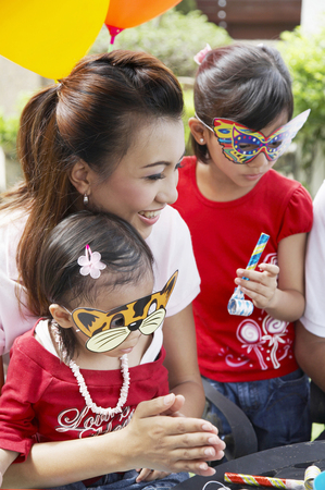 woman with two girls wearing party masks Stok Fotoğraf