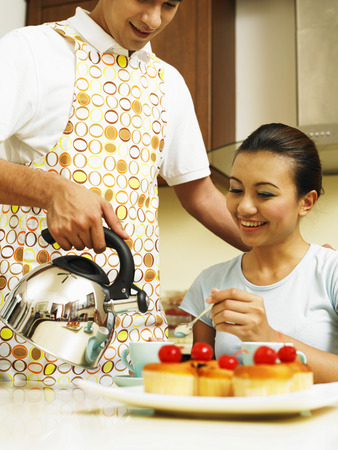 couple making tea in the kitchen Imagens