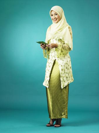 Single malay woman handing out envelop Banco de Imagens - 119357095