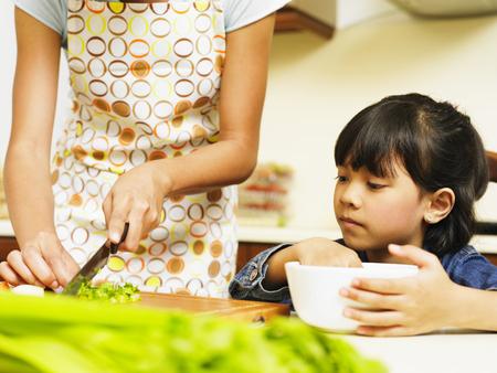 Daughter watching mother preparing food Imagens
