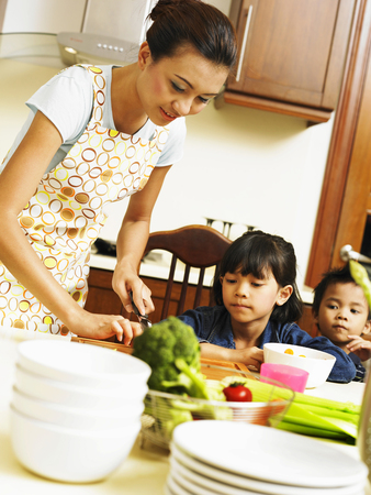 Mother and children preparing meal in the kitchen Imagens