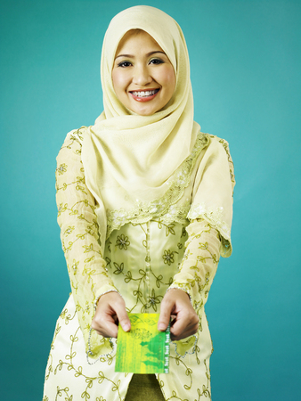 Single malay woman handing out envelop Banco de Imagens - 119357911