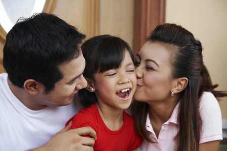 parent kissing their daughter on her cheek Stock Photo